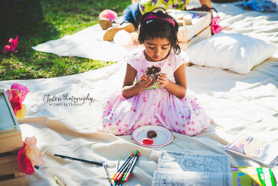 little girl eating cupcake at a baby shower in the park