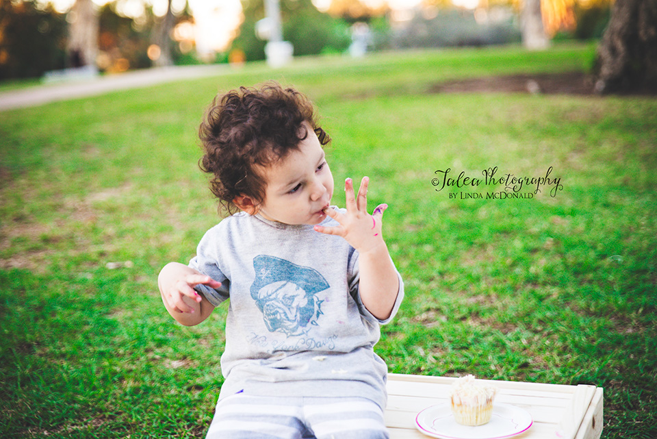 little boy eating cupcake at a baby shower in the park