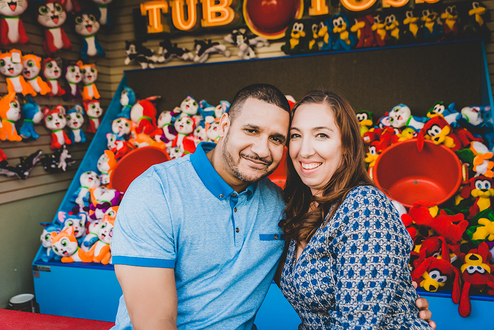engaged couple sitting by amusement games Belmont Park San Diego