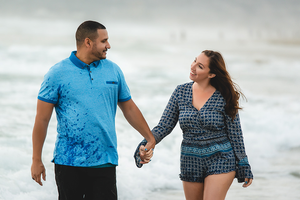 engaged couple walking by the water at Mission Beach San Diego