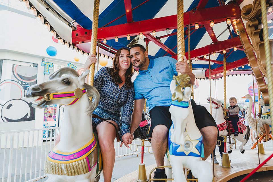 engaged couple riding carousel Belmont Park San Diego photo shoot