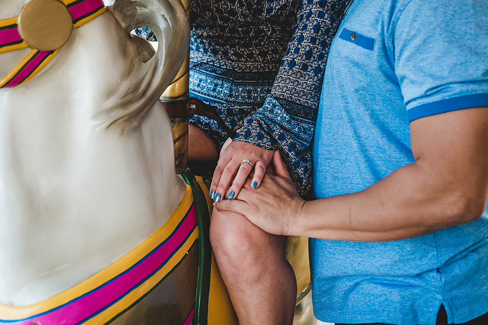 hands of engaged couple showing ring on carousel Belmont Park San Diego photo shoot