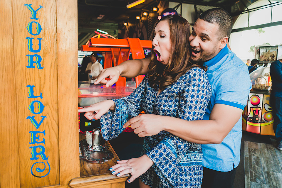 engaged couple showing excitement playing games Belmont Park San Diego