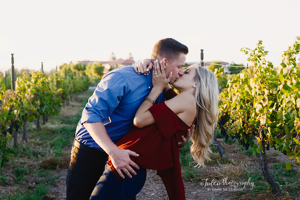 engaged-couple-kissing-vineyard-in-South-Coast-Winery-resort