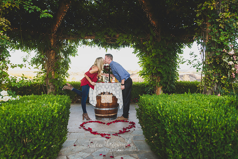 couple kissing in Rose Arbor at South Coast Winery Temecula