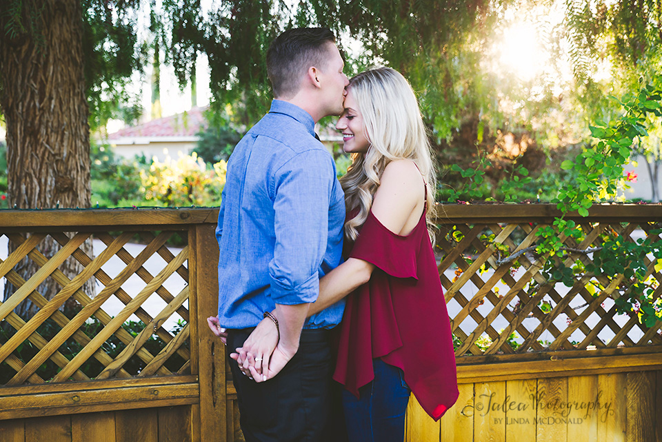 guy kissing fiancee on forehead Temecula winery proposal