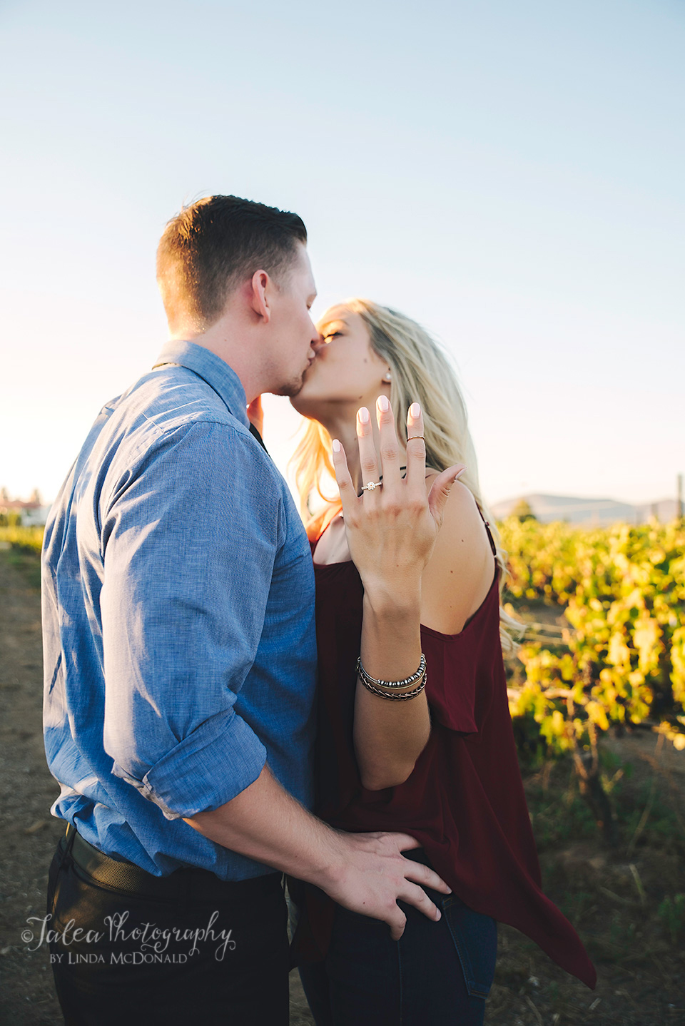couple kissing in vineyard showing off engagement ring Temecula winery proposal