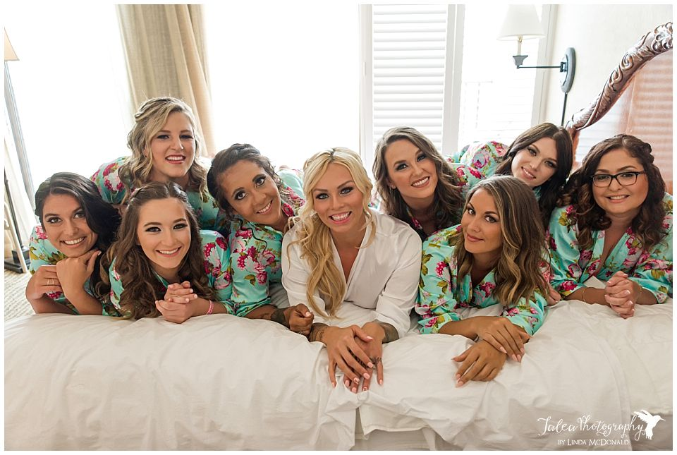 bride-and-bridesmaids-lying-on-bed-in-robes