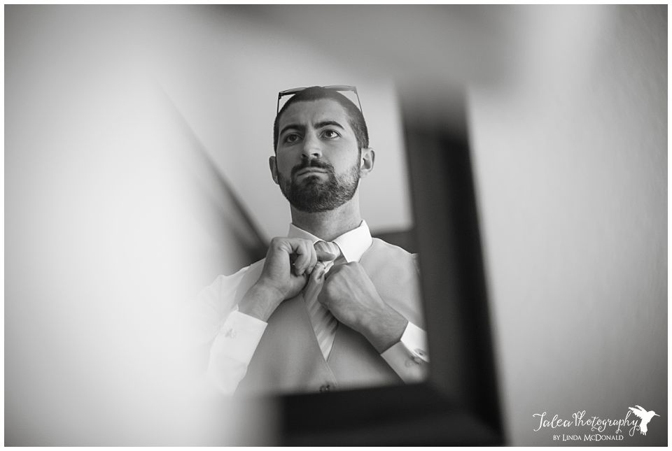 groom-adjusting-his-tie-in-the-mirror