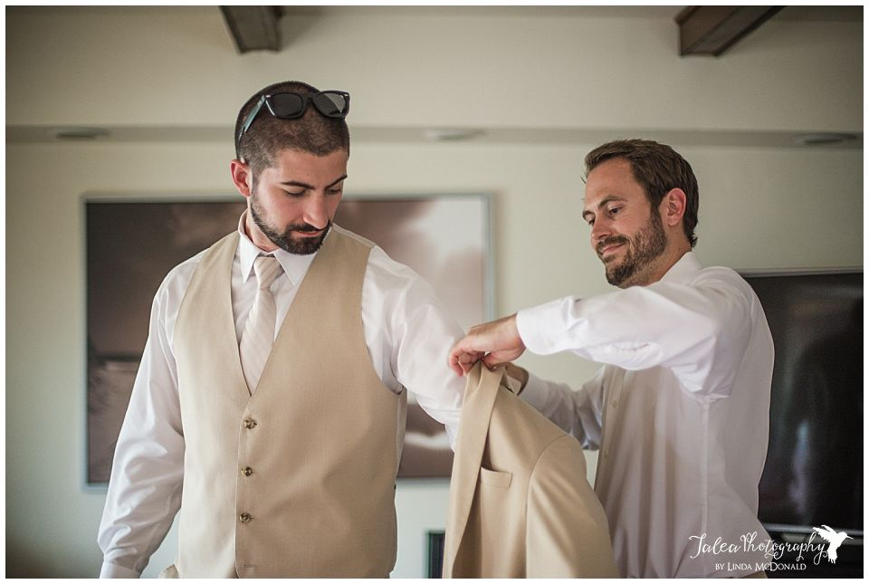 groomsmen-helping-groom-put-on-jacket