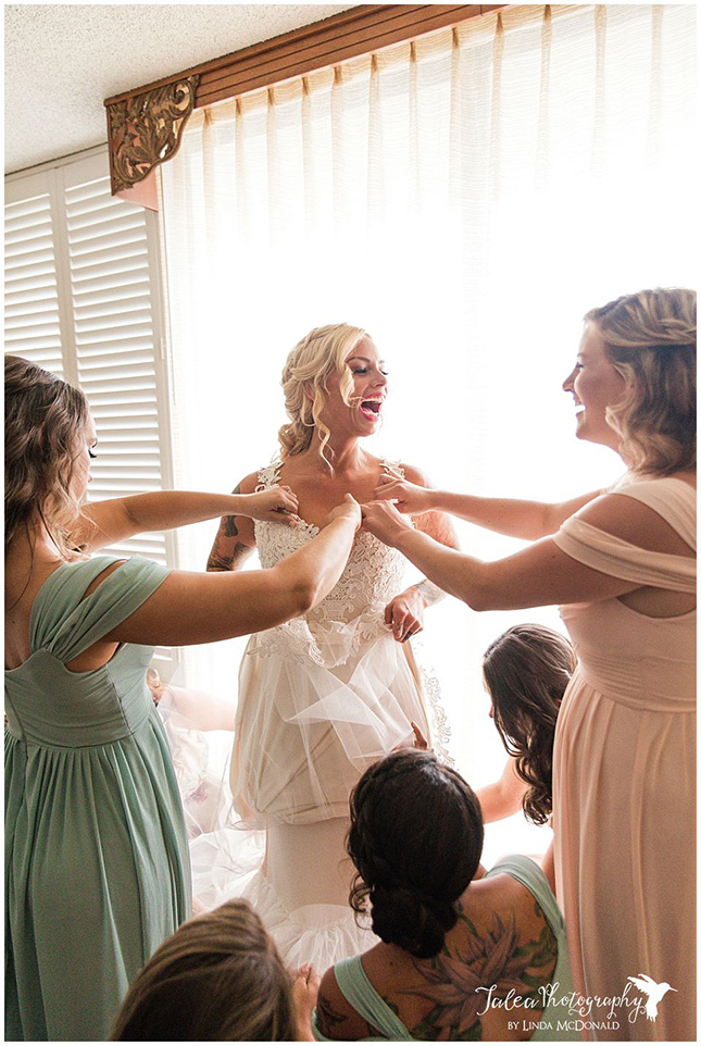 bridesmaid-adjusting-bride's-dress-while-she-is-laughing