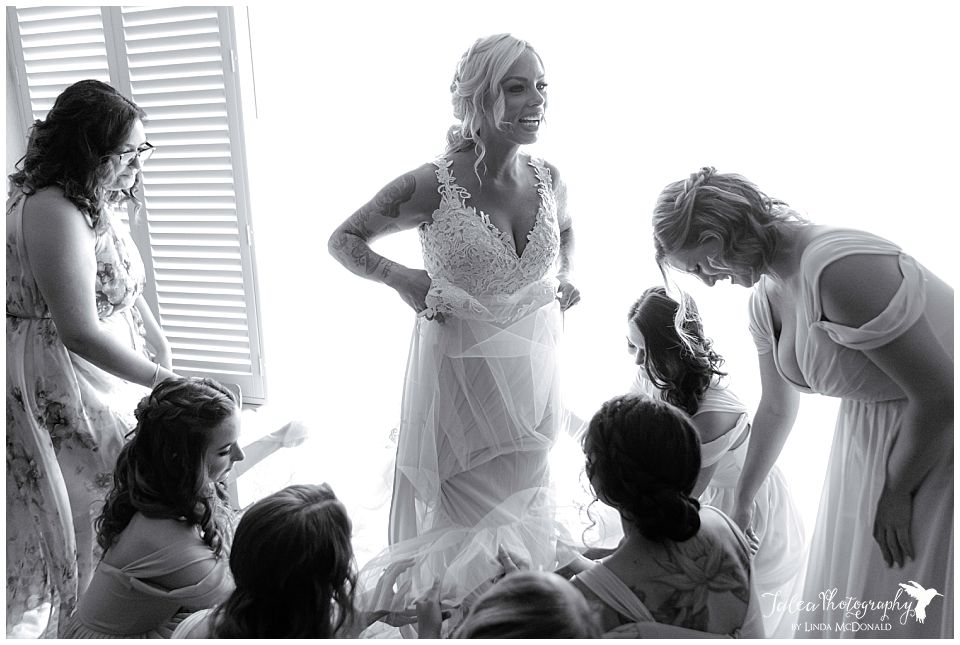 bride-having-her-dress-adjusted-by-bridesmaids