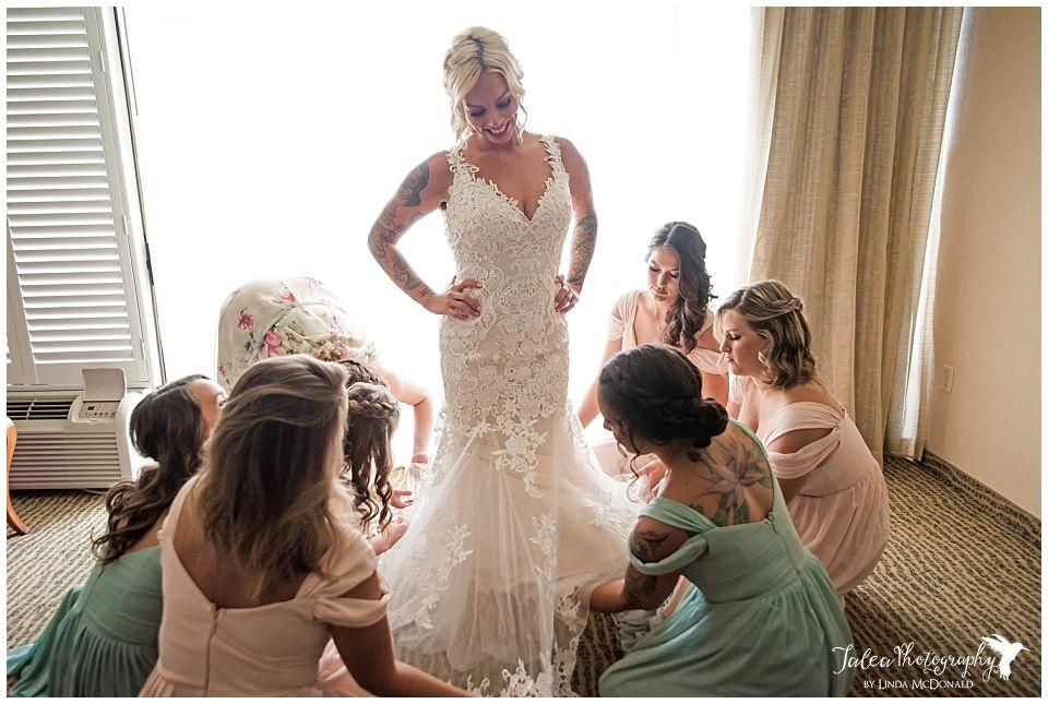 bridesmaid-adjusting-bride's-dress