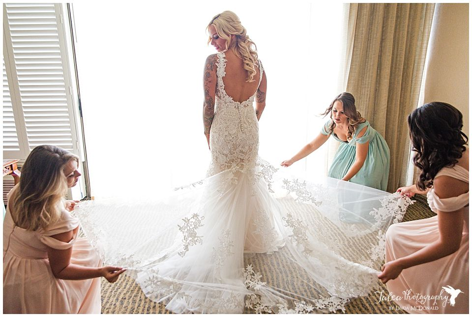bridesmaids-adjusting-back-of-bride's-dress