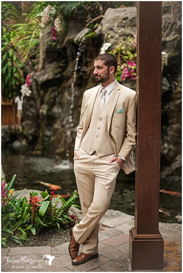 groom-standing-by-waterfall-at-catamaran-resort-san-diego