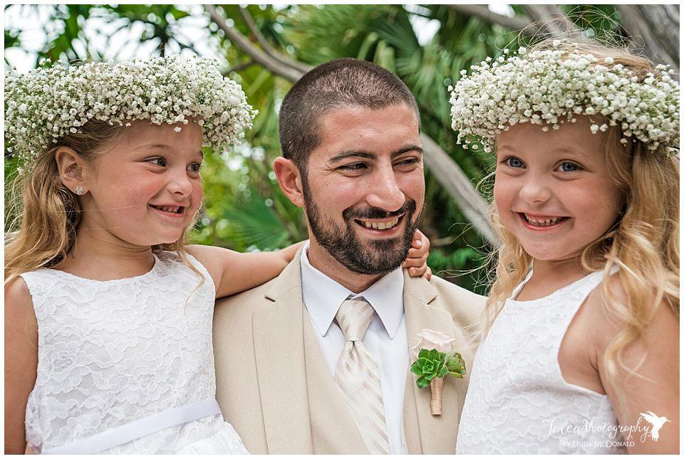 groom-holding-flower-girls