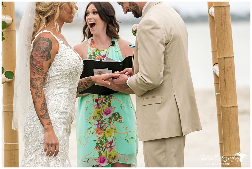 groom-putting-ring-on-bride-officiant-surprised-face-in-background