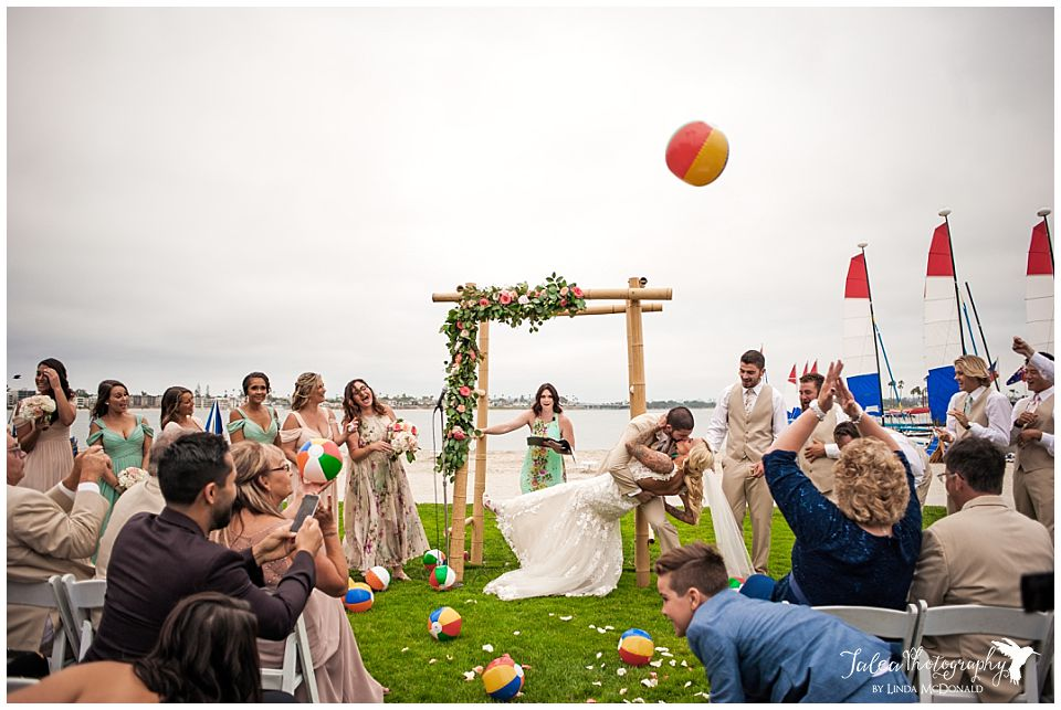 groom-dipping-bride-at-catamaran-san-diego-wedding-ceremony-for-first-kiss