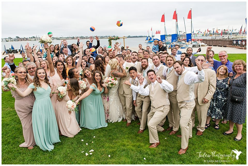 catamaran-resort-san-diego-wedding-large-group-photo-bride-groom-kissing