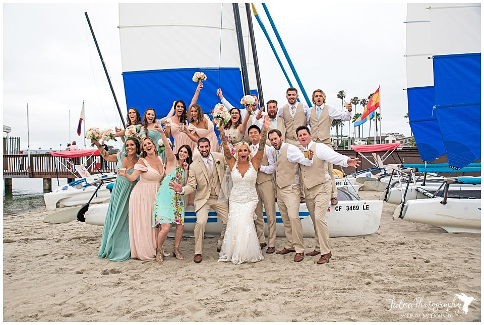 bridal-party-cheering-posing-on-top-of-sailboard-catamaran-resort-san-diego