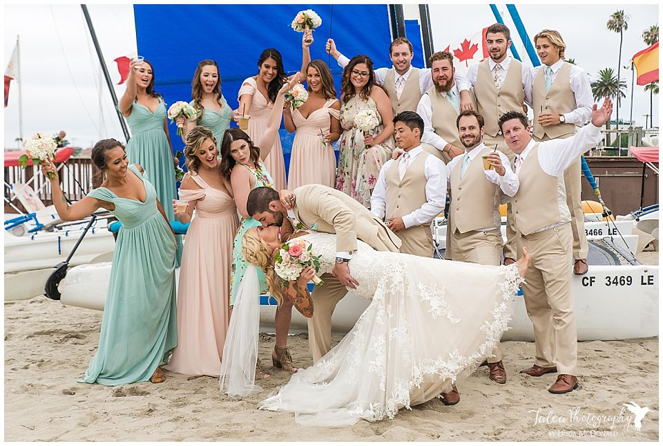 san-diego-catamaran-resort-groom-dipping-bride-surrounded-by-bridal-party