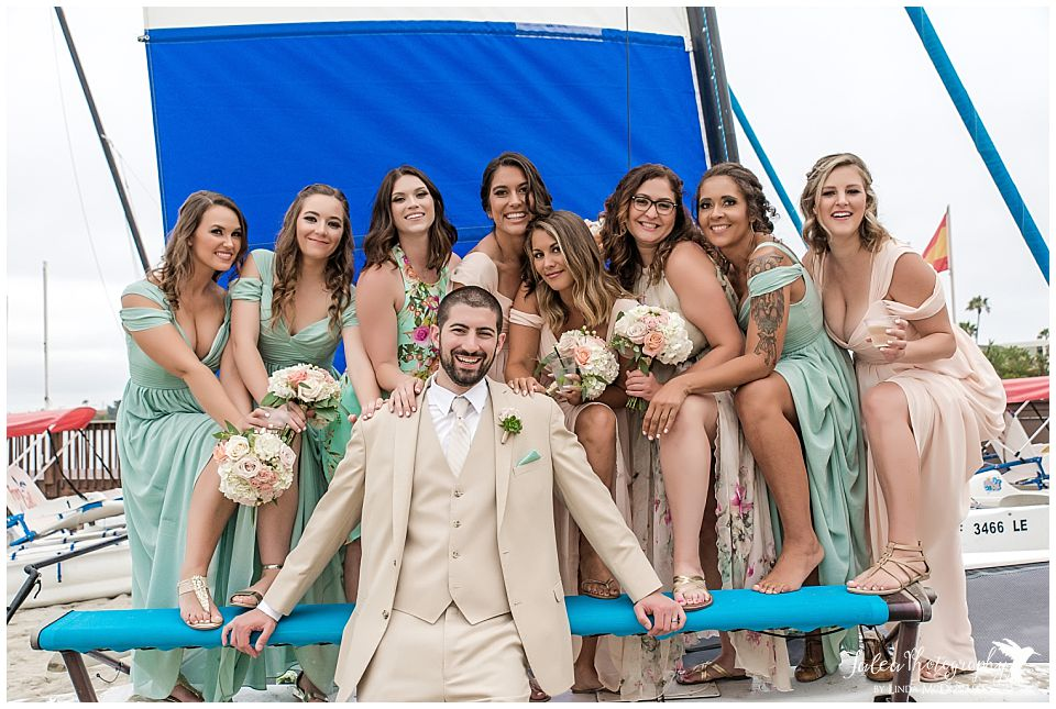 wedding-catamaran-mission-bay-groom-standing-with-bridesmaid-on-sailboat