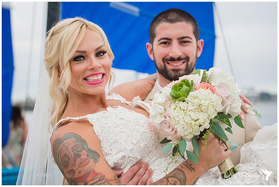 groom-holding-bride-both-looking-into-the-catamaran-beach-front-wedding