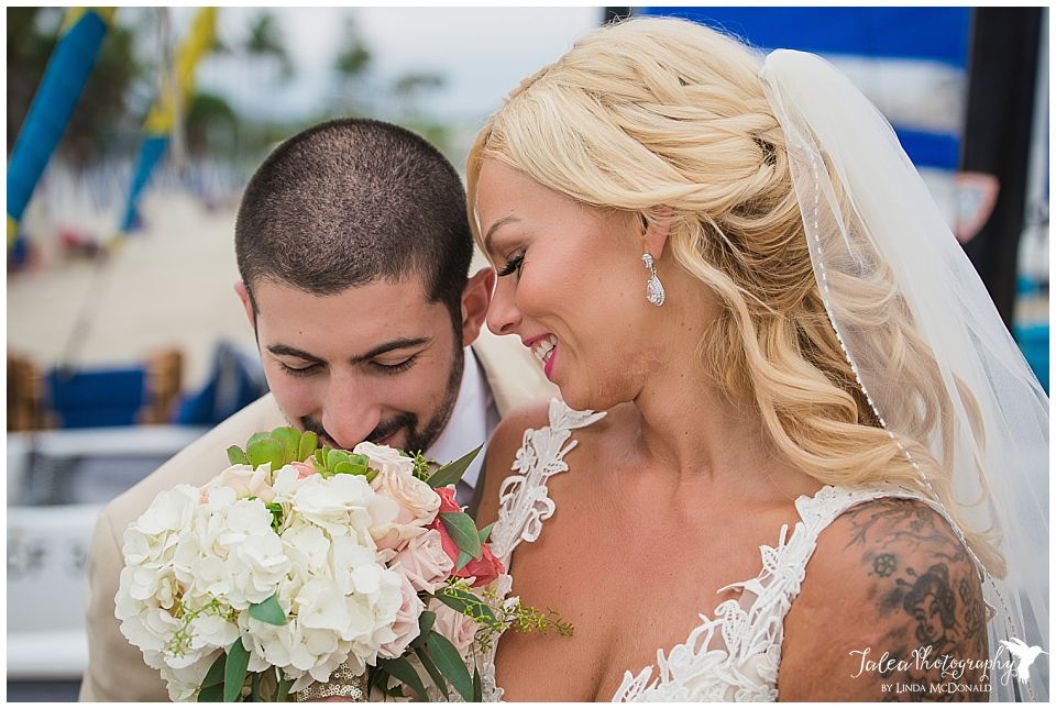 beach-wedding-groom-smelling-bridal-bouquet