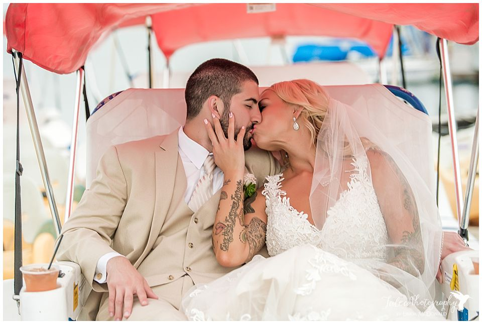 bride-groom-kissing-on-small-canopy-boat-mission-bay-wedding