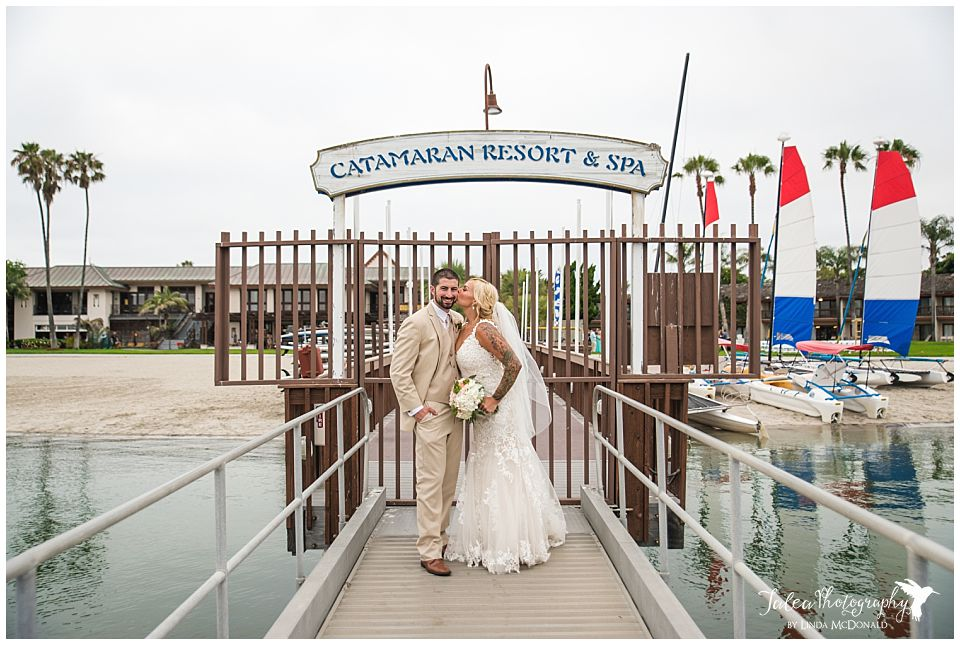 catamaran-resort-spa-san-diego-bride-kissing-groom-in-front-of-sign