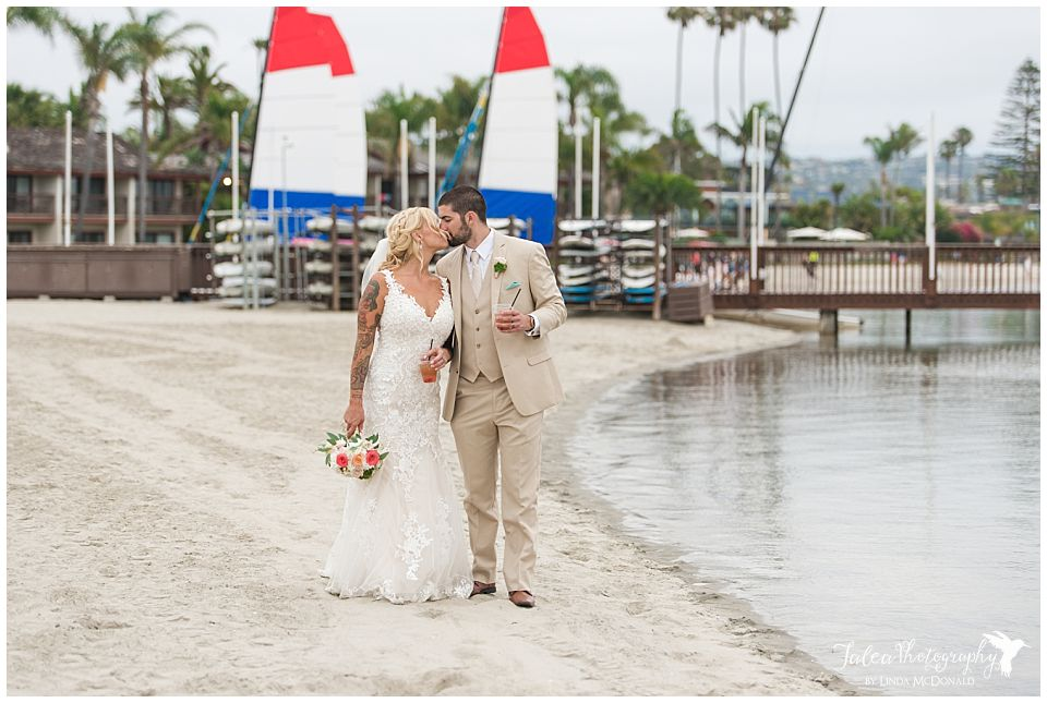 bride-groom-kissing-holding-cocktails-san-diego-mission-bay