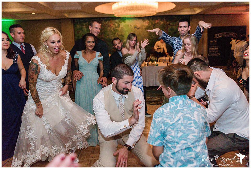 bride-looking-on-as-groom-dances-at-wedding-reception