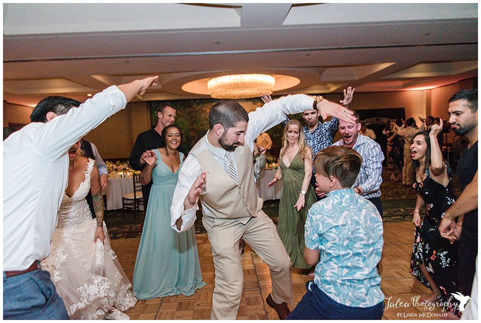 groom-encircle-by-guest-while-dancing