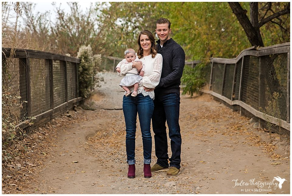 family of three posing for portraits on trail path in san diego