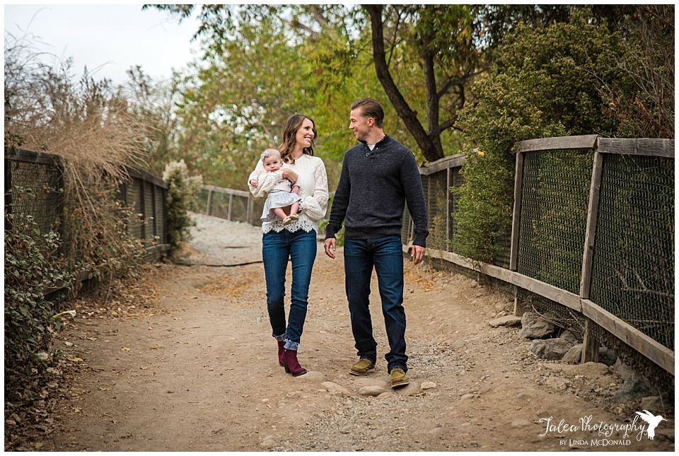 young couple holding an infant walking on san diego trail path for portraits