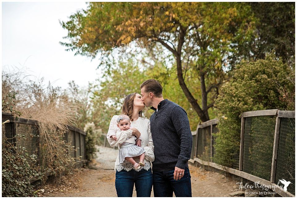 portrait of couple kissing on san diego trail path and holding baby