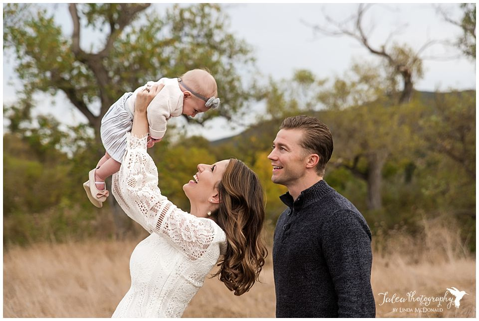mother holding baby in air while dad is watching for family portraits in san diego