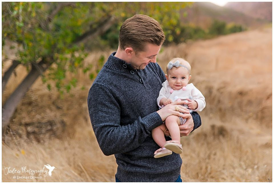 smiling dad holding baby for portrait in grassy field san diego