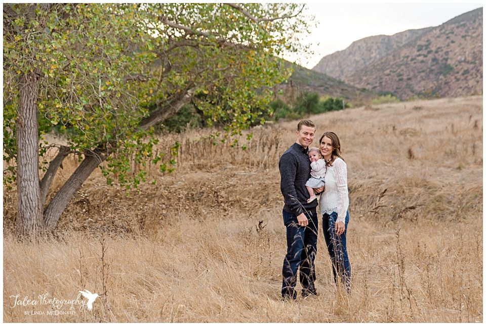 couple-with-baby-in-middle-standing-next to-tree-in-grassy-field