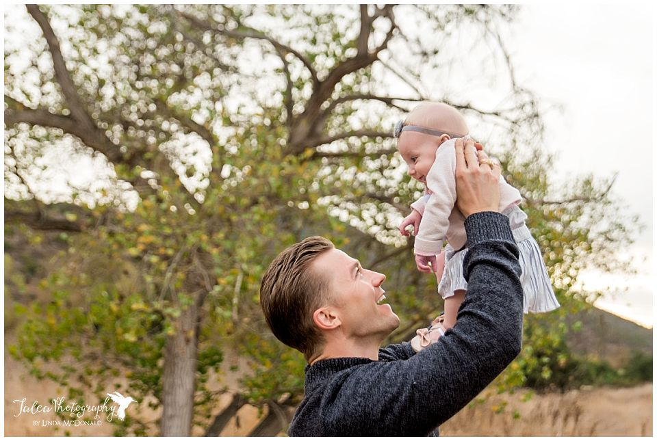 daddy-holding-baby-up-in-the-air-in-front-of-a-tree-smiling