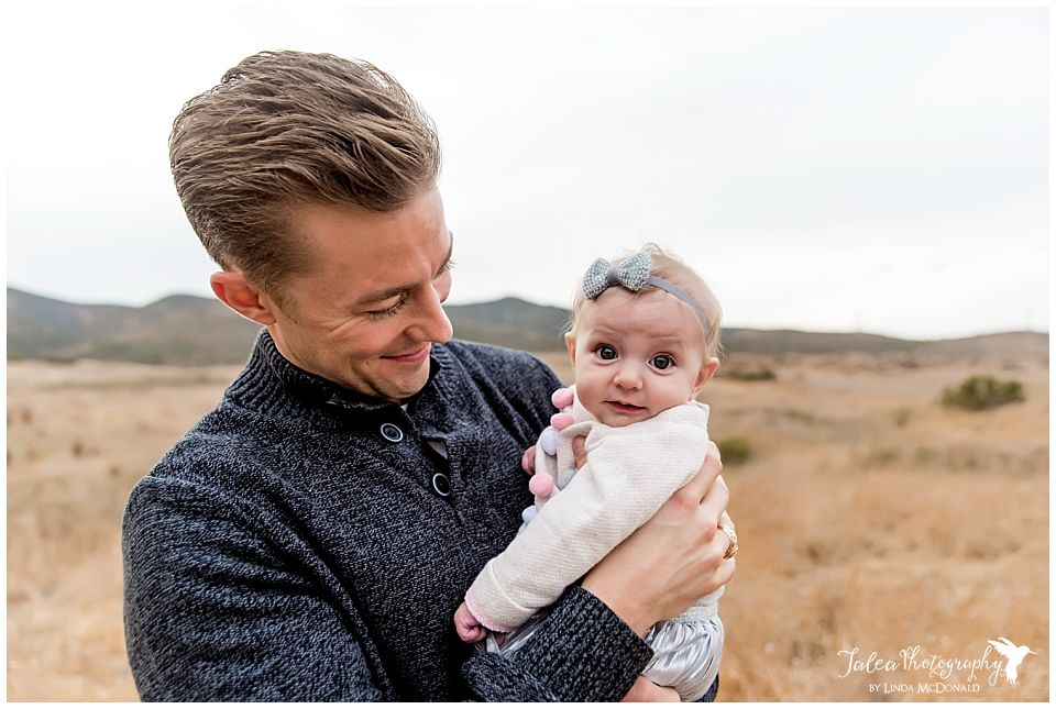 bright eyed baby held by dad in large open field for family portaits in san diego