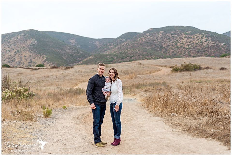 family of three posing on trails path for family photos in san diego