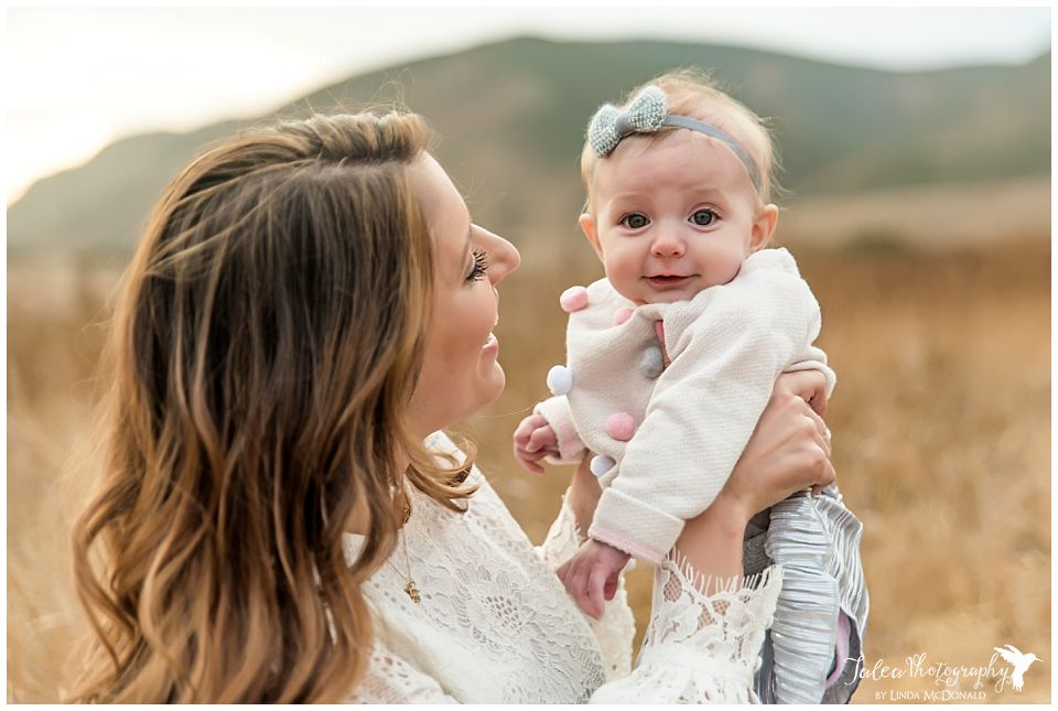 family photo shoot in san diego portait of mom smiling and holding baby