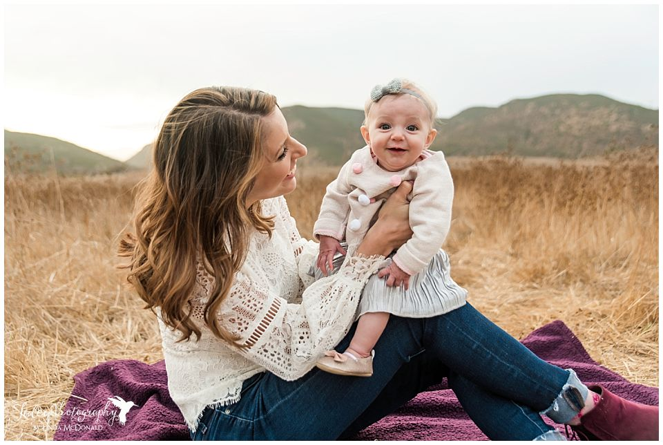 mom and baby sitting on blanket smiling for family photos in san diego