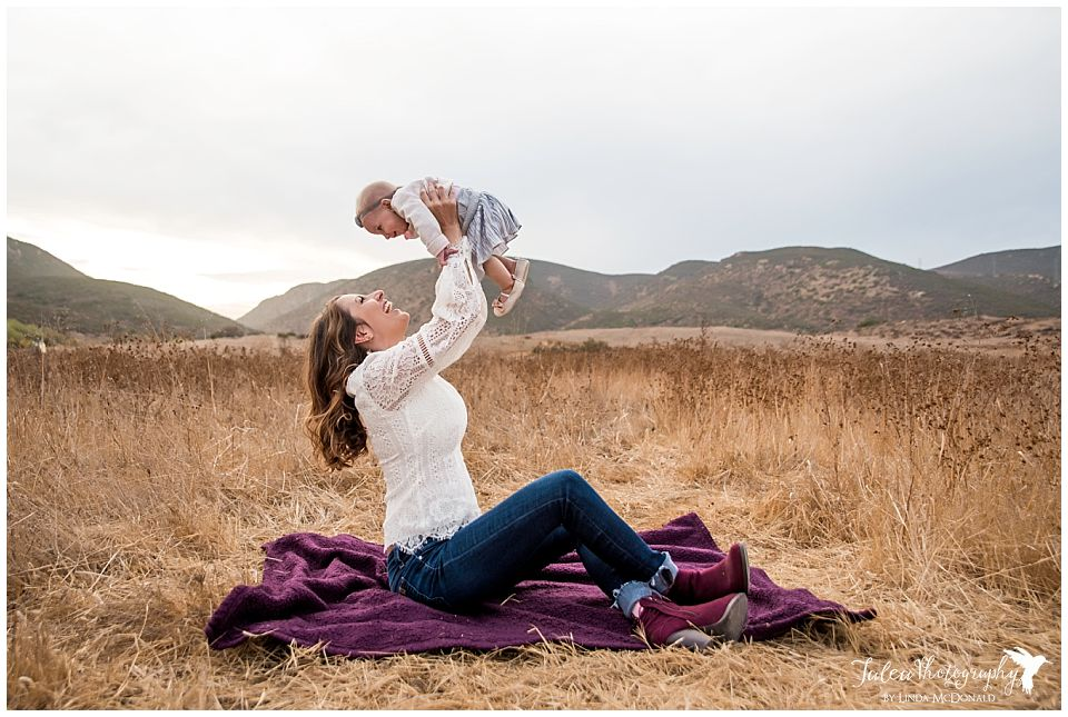 mama-sitting-on-blanket-holding-baby-up-in-air-san-diego-photographer