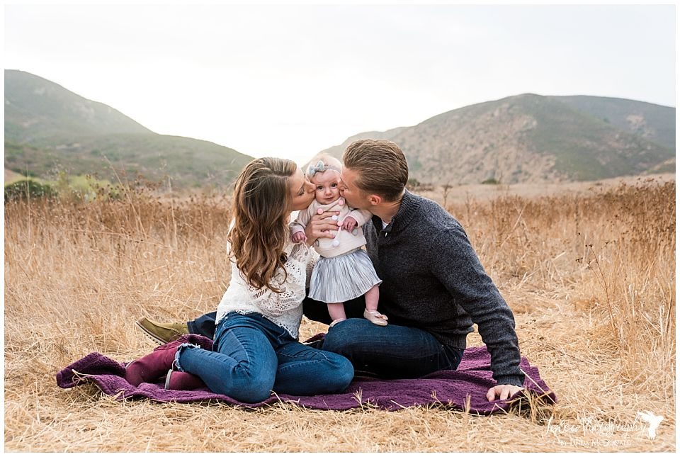 couple sitting on blanket kissing baby on cheek for san diego family portrait photographer