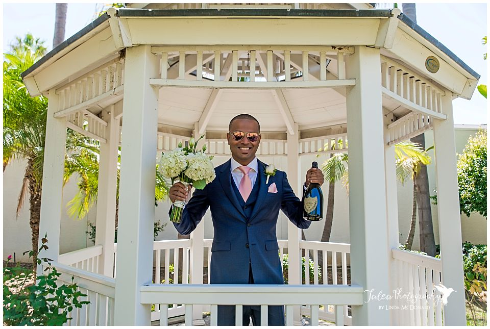 groom-holding-champagne-bouquet-standing-in-gazebo