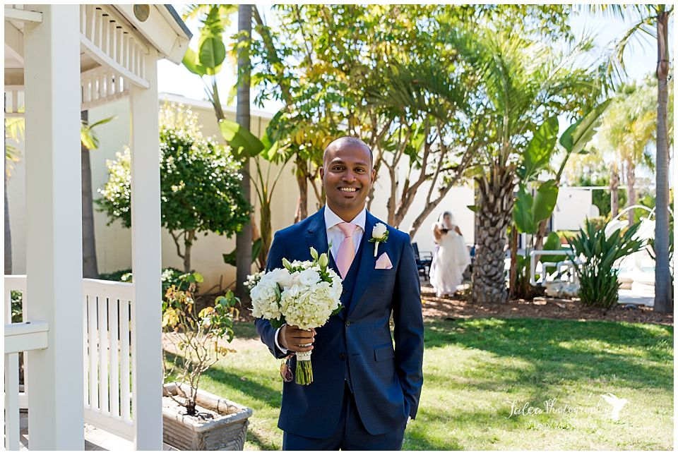 groom-smiling-while-bride-is-approaching-for-first-look