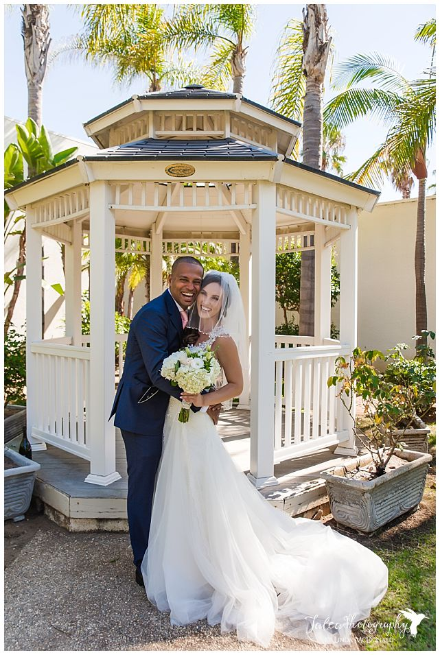 bride-and-groom-standing-near-gazebo-smiling-embracing