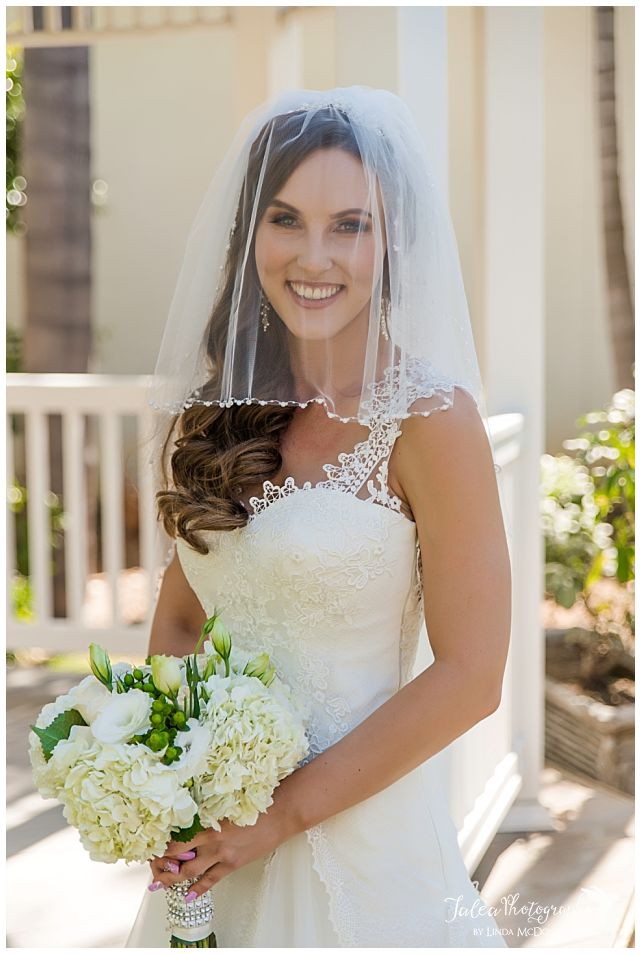 bride-with-veil-smiling-in-front-of-gazebo